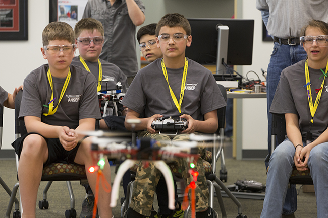 Sorin Sorensen pilots his team's UAV while teammates look on during ANSEP's STEM Career Explorations in June 2015